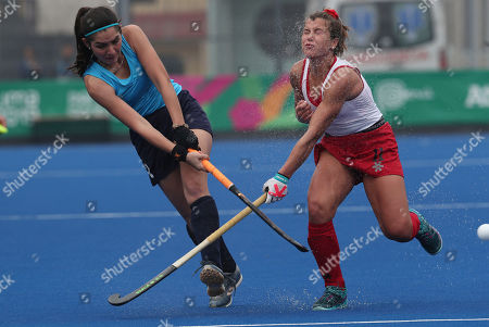 Stock Image of Maria Villar, Amanda Woodcropt. Maria Villar of Uruguay, left, hits the ball as Amanda Woodcropt of Canada is splashed with water from a water-soaked pitch, during a field hockey women's preliminaries match, at the Pan American Games in Lima, Peru