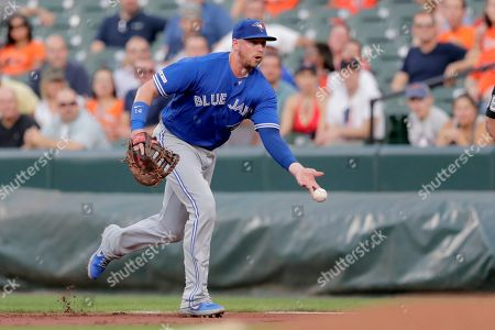 Toronto Blue Jays first baseman Justin Smoak tosses to starting pitcher Trent Thornton to put out a Baltimore Orioles batter during the first inning of a baseball game, in Baltimore