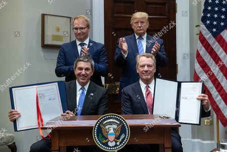Stock Picture of US President Donald J. Trump (R) and Jani Raappana (L), Deputy Head of Mission, for the Finnish Presidency of the Council of the EU, applaud as US Trade Representative Robert Lighthizer (bottom right), and Stavros Lambrinidis, the Ambassador of the European Union to the United States, hold up a signed agreement for US beef exports to the European Union, in the Roosevelt Room at the White House in Washington, DC, USA, 02 August 2019.