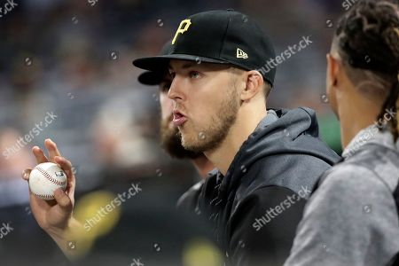 Pittsburgh Pirates starting pitcher Jameson Taillon, center, sits in the dugout during a baseball game against the New York Mets in Pittsburgh, . The Pirates won 8-4. It was announced before the game by a team trainer that Taillon will not require Tommy John surgery