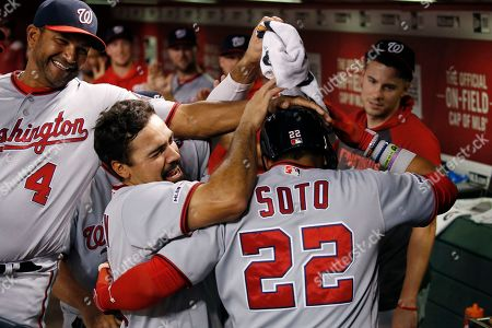 Stock Image of Washington Nationals' Juan Soto (22) celebrates his home run against the Arizona Diamondbacks with manager Dave Martinez (4), Anthony Rendon, second from left, and Patrick Corbin, right, during the eighth inning of a baseball game, in Phoenix