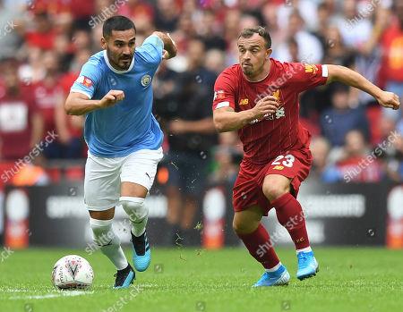 Ilkay Gundogan of Manchester City chased by Xherdan Shaqiri of Liverpool