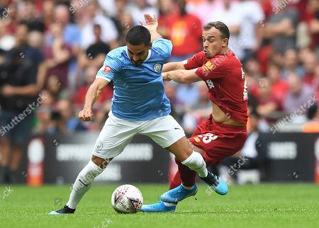 Xherdan Shaqiri of Liverpool grabs Ilkay Gundogan of Manchester City