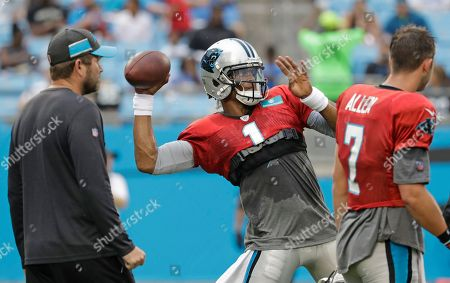 Stock Photo of Carolina Panthers' Cam Newton (1) looks to pass as quarterbacks coach Scott Turner, left, watches during a Fan Fest practice at the NFL football team's training camp in Charlotte, N.C