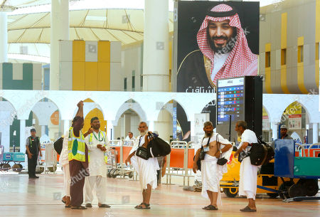 Pilgrims walk under a giant poster showing Saudi Crown Prince Mohammed bin Salman as they arrive at the Hajj Terminal at Jiddah airport, Saudi Arabia, . The annual Islamic pilgrimage draws millions of visitors each year, making it the largest yearly gathering of people in the world