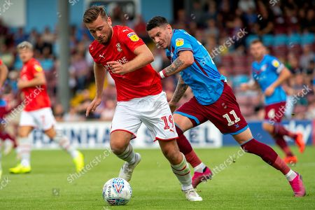 Jordan Lyden of Swindon Town runs ahead of Adam Hammill of Scunthorpe United during the EFL Sky Bet League 2 match between Scunthorpe United and Swindon Town at Sands Venue Stadium, Glanford Park, Scunthorpe