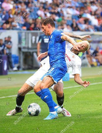 Hoffenheim's Steven Zuber (front) in action against Sevilla's Lucas Ocampos (back) during the friendly soccer match between TSG 1899 Hoffenheim and Sevilla FC in Sinsheim, Germany, 03 August 2019.
