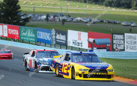 Kyle Busch (18) closely pursues Ryan Blaney (12) just before spinning out in a NASCAR Xfinity Series auto race at Watkins Glen International, in Watkins Glen, New York