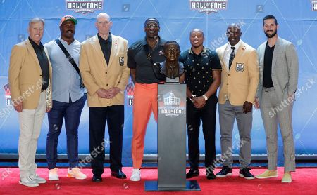 Former NFL players John Elway, Von Miller, Gary Zimmerman, Shannon Sharpe, Chris Harris Jr., Terrell Davis and Brandon McManus, from left, pose with the bust of former Denver Broncos owner Pat Bowlen during the induction ceremony at the Pro Football Hall of Fame, in Canton, Ohio