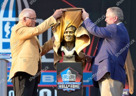 Former NFL player Johnny Robinson, left, unveils his bust with presenter Bob Thompson during the induction ceremony at the Pro Football Hall of Fame, in Canton, Ohio
