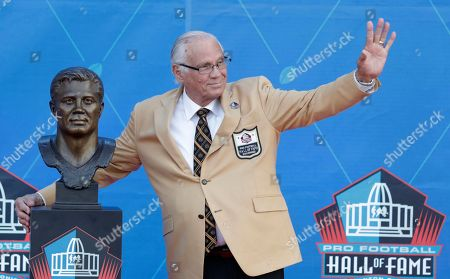 Former NFL player Johnny Robinson waves as he poses with his Pro Football Hall of Fame bust during inductions at the hall, in Canton, Ohio