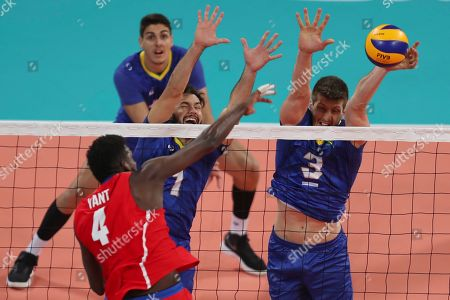 Stock Picture of Eder Carbonera of Brazil block a spike from Marlon Yang of Cuba in their men's volleyball semifinal match at the Pan American Games in Lima, Peru