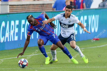 Stock Image of FC Cincinnati's Roland Lamah (7) goes for the ball against Vancouver's Felipe Martins (8) during an MLS soccer game between FC Cincinnati and Vancouver Whitecaps at Nippert Stadium in Cincinnati, Ohio
