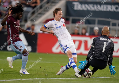 Colorado Rapids goalkeeper Tim Howard (1) makes a save against Montreal Impact midfielder Lassi Lappalainen, center, as Rapids defender Lalas Abubakar, left, looks on during the first half of an MLS soccer match, in Commerce City, Colo