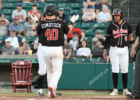 FM Redhawks catcher Daniel Comstock (40) celebrates hitting a three run homer as he crosses home plate during the FM Redhawks game against the Winnipeg Goldeyes in American Association professional baseball at Newman Outdoor Field in Fargo, ND. The Redhawks won 8-4