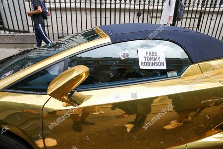 Supporters of Stephen Yaxley-Lennon, known as Tommy Robinson stick a sticker on a parked golden Lamborghini in central London
