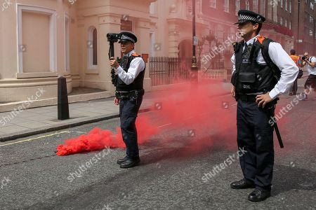 A flare is thrown at the police by anti Tommy Robinson protesters during a protest in central London