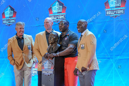 Stock Image of rd, John Elway, Shannon Sharpe, Terrell Davis posing with Pat Bowlen's bust during the Pro Football Hall of Fame Enshrinement in Canton, OH