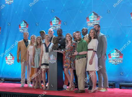 Stock Picture of rd, John Elway, Von Miller, Shannon Sharpe, Terrell Davis, Chris Harris, Eric Decker, and Bowlen family posing with Pat Bowlen's bust during the Pro Football Hall of Fame Enshrinement in Canton, OH