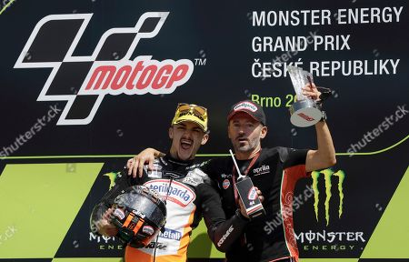 Spain's rider Aron Canet of the Sterilgarda Max Racing Team, left, celebrates with Max Biaggi on the podium after winning the Moto3 race at the Czech Republic motorcycle Grand Prix at the Automotodrom Brno, in Brno, Czech Republic