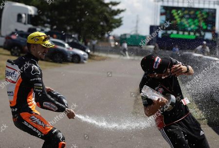 Spain's rider Aron Canet of the Sterilgarda Max Racing Team, left, celebrates and sprays champagne Max Biaggi after winning the Moto3 race at the Czech Republic motorcycle Grand Prix at the Automotodrom Brno, in Brno, Czech Republic