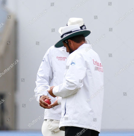 Umpires Aleem Dar and Joel Wilson check to see if the ball has gone out of shape by putting it through the two metal rings they carry