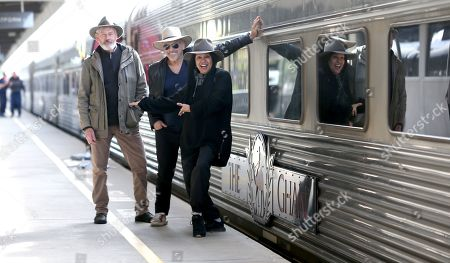 Stock Photo of Shane Howard, Joe Camilleri and Christina Anu pose for a photograph on the platform before departing for Darwin with the Australian passenger train The Ghan, in Adelaide, South Australia, Australia, 04 August 2019. The Ghan train service marks 90 years of operations on 04 August 2019, with a special service leaving Adelaide for Darwin. The transcontinental railway service runs between the cities of Adelaide, Alice Springs and Darwin traveling on the Adelaide-Darwin railway for 2,979 km.