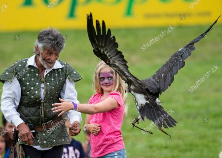 Savannah Phillips with her face painted, gets to meet a vulture during the Bird of Prey display, with falconer Ray Aliker
