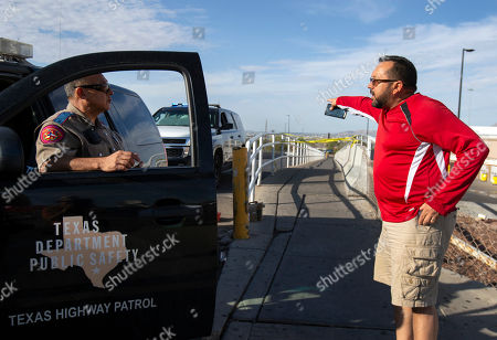 Stock Image of Carlos Santos, right, argues with a Texas State trooper, as he's unable to retrieve his vehicle from the Walmart parking lot in the aftermath of a mass shooting in El Paso, Texas