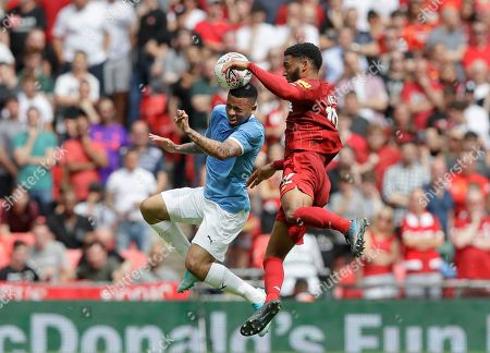 Manchester City's Gabriel Jesus, left, jumps for a header with Liverpool's Joe Gomez during the English Community Shield soccer match between Liverpool and Manchester City at Wembley stadium in London