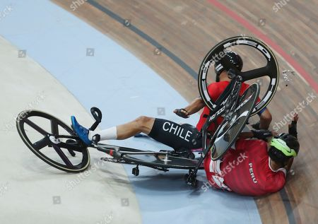 Antonio Cabrera, top, of Chile and Renato Tapia of Peru fall during for track cycling men's madison at the Pan American Games in Lima, Peru