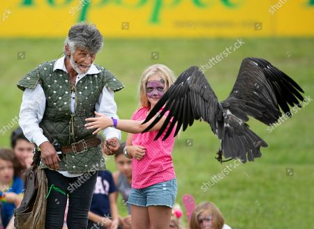 Stock Photo of Savannah Phillips with her face painted, gets to meet a vulture during the Bird of Prey display, with falconer Ray Aliker