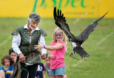 Stock Image of Savannah Phillips with her face painted, gets to meet a vulture during the Bird of Prey display, with falconer Ray Aliker
