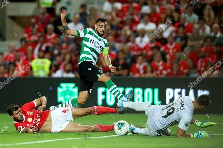 Bruno Fernandes of Sporting CP (C) vies for the ball with Ruben Dias of SL Benfica (L) and Odysseas Vlachodimos of SL Benfica (R)
