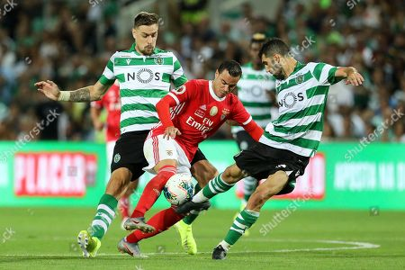 Raul de Tomás of SL Benfica (C) vies for the ball with Sebastian Coates of Sporting CP (L) and Luís Neto of Sporting CP (R)