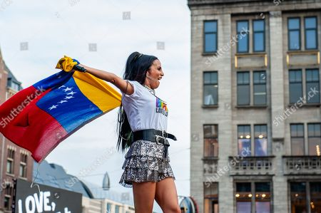 Venezuelan singer, songritten and actress Mayre Martinez is seen holding a Venezuelan flag. The official end party where there is always a colourful collection of artists enters the stage took place at the famous Dam square in Amsterdam. This year?s performances of Conchita, Mutya Buena, Netta, Paul Morris, Mayré Martinez, Channah Hewitt, etc and hosting by one of the Pride ambassadors, Amber Vineyard.
