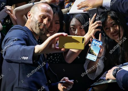 Stock Picture of Actors Jason Statham takes a selfie with fans during the red carpet event ahead of the premiere of 'Fast & Furious: Hobbs & Shaw' in Beijing