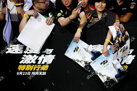 Chinese fans hold posters as they wait for actors Jason Statham and Dwayne Johnson during the red carpet event ahead of the premiere of 'Fast & Furious: Hobbs & Shaw' in Beijing