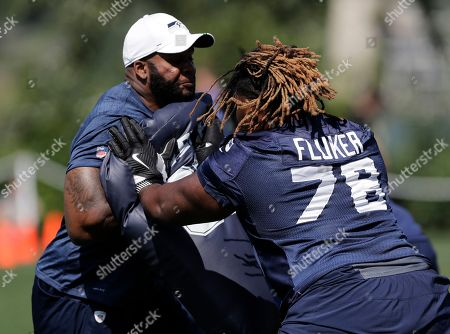 Seattle Seahawks offensive guard D.J. Fluker, right, hits a blocking pad during NFL football training camp, in Renton, Wash