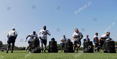 Seattle Seahawks defensive players, including tackles Earl Mitchell (75) and Jamie Meder (66) run drills during NFL football training camp, in Renton, Wash