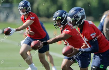 Seattle Seahawks quarterback Russell Wilson, center, drops back next to passes next to backup quarterbacks Paxton Lynch, left, and Geno Smith, right, during NFL football training camp, in Renton, Wash