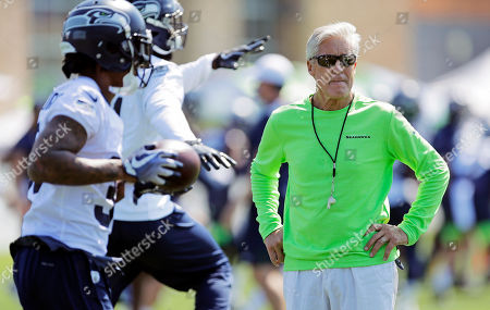 Seattle Seahawks head coach Pete Carroll looks on as defensive players run drills during NFL football training camp, in Renton, Wash