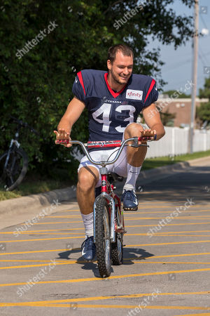 Houston Texans safety Chris Johnson rides a fans bike to a joint NFL football practice with the Green Bay Packers, in Green Bay, Wis