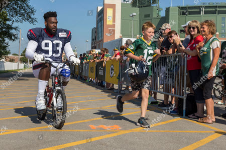 Houston Texans defensive end Joel Heath rides a fans bike to a joint NFL football practice with the Green Bay Packers, in Green Bay, Wis