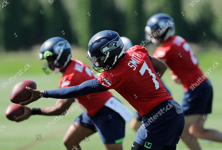 Seattle Seahawks backup quarterback Geno Smith (7) runs a drill with staring quarterback Russell Wilson and backup quarterback Paxton Lynch during NFL football training camp, in Renton, Wash
