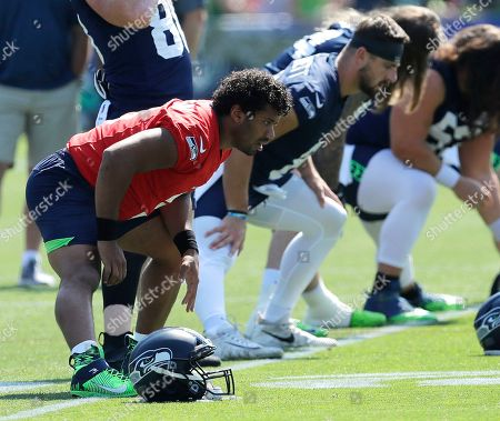 Seattle Seahawks quarterback Russell Wilson, left, stretches during NFL football training camp, in Renton, Wash