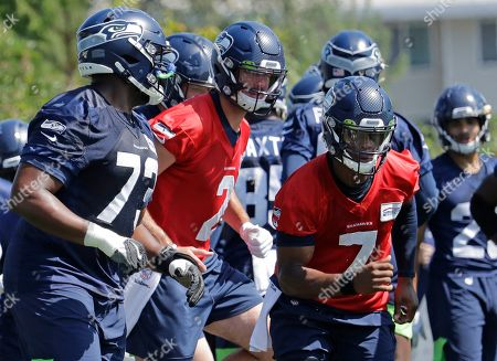 Seattle Seahawks backup quarterbacks Geno Smith (7) and Paxton Lynch (2) run with other players during NFL football training camp, in Renton, Wash