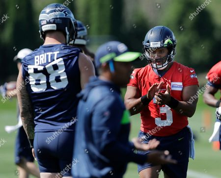 Seattle Seahawks quarterback Russell Wilson, right, takes part in a drill during NFL football training camp, in Renton, Wash