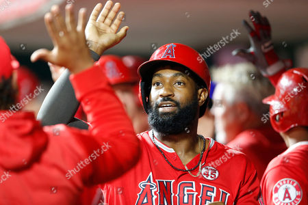 Los Angeles Angels' Brian Goodwin (18) smiles as he is congratulated in the dugout following a two-run home run off Cincinnati Reds relief pitcher David Hernandez during the ninth inning of a baseball game, in Cincinnati
