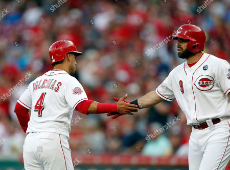 Cincinnati Reds' Jose Iglesias (4) is congratulated by Jose Peraza, right, after scoring on a single by Nick Senzel off Los Angeles Angels starting pitcher Taylor Cole during the inning of a baseball game, in Cincinnati